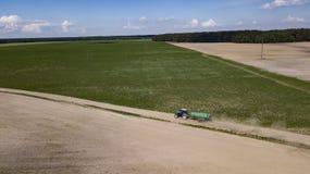 拖拉机在领域的被驾驶的有机肥料 库存照片