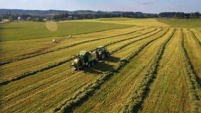 拖拉机天线在山的晴天做干草捆并且投下他们盖了在塑料 股票视频
