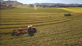 拖拉机天线在山的晴天做干草捆并且投下他们盖了在塑料 股票录像
