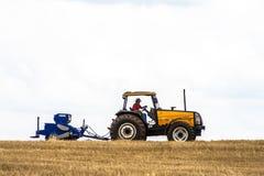 拖拉机播种庄稼的农夫在领域 图库摄影