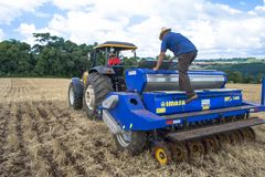拖拉机播种庄稼的农夫在领域 免版税库存照片