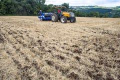 拖拉机播种庄稼的农夫在领域 免版税库存图片