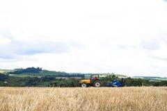 拖拉机播种庄稼的农夫在领域 免版税图库摄影