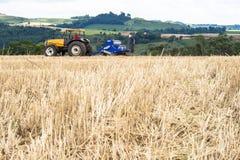 拖拉机播种庄稼的农夫在领域 库存照片