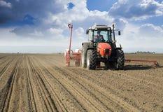 拖拉机播种庄稼的农夫 免版税图库摄影