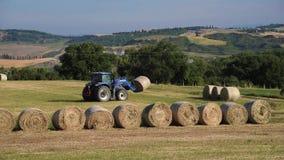 拖拉机收集有干草的大包在领域 股票录像