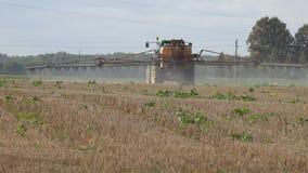拖拉机浪花与除草药化学制品的亩茬地在秋天 图库摄影