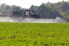 拖拉机浪花施肥与杀虫药在农业领域的除草药化学制品 免版税库存照片