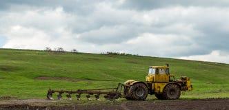 拖拉机犁领域的土地在春天 免版税库存图片