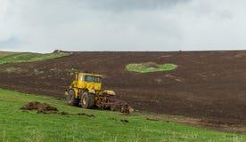 拖拉机犁领域的土地在春天 免版税图库摄影