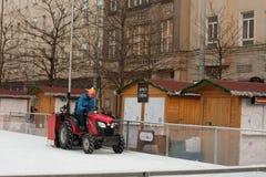 拖拉机的人清洗人为滑冰场 免版税库存照片