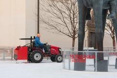 拖拉机的人清洗人为滑冰场 图库摄影