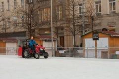 拖拉机的人清洗人为滑冰场 免版税图库摄影