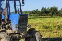 拖拉机的前面是大在一个绿色草甸的背景 库存照片