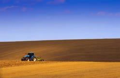 拖拉机的土地在天蓝色下树荫的。 免版税库存照片