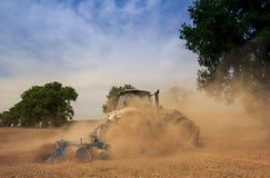 拖拉机耕地机培养在被耕的领域的伟大的尘土 免版税库存照片