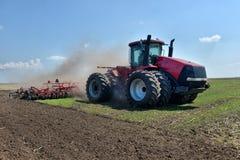 拖拉机运转在领域的,在工作的农机, 库存图片