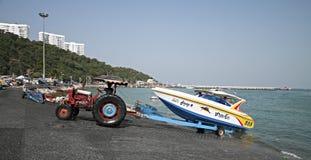 拖拉机运输从海的一条小船海滩 图库摄影