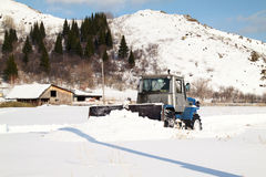 拖拉机从雪清洗路在村庄 免版税库存图片