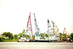 拖曳与起重机的小船或货船在河沿口岸 免版税库存照片
