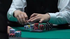 拖曳卡片的副主持人对打牌者,赌博娱乐场在桌上切削,赌博 股票录像