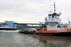 拖曳小船在荷兰语河拉无舵的货轮 免版税库存照片