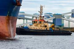 拖曳蓝色散装货轮的猛拉船 图库摄影