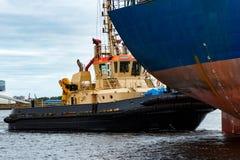 拖曳蓝色散装货轮的猛拉船 免版税库存照片