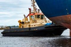 拖曳蓝色散装货轮的猛拉船 免版税库存图片