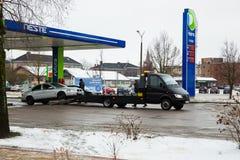 拖车和残破的富豪集团汽车在街道 冬天和雪,燃料驻地 都市旅行照片2018年 免版税库存照片