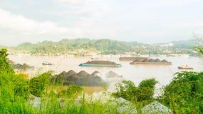 拖轮交通美丽的景色拉扯煤炭的驳船在马哈坎河,沙马林达,印度尼西亚 免版税图库摄影