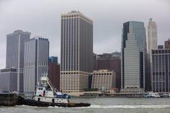 拖轮在有曼哈顿的NYC河在背景中 库存照片