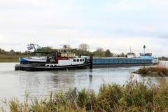 拖轮在荷兰语河扯拽无舵的货轮 免版税库存图片