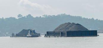 拖轮拉扯煤炭重的被装载的驳船  库存照片