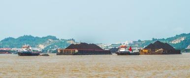拖轮繁忙运输拉扯煤炭重的被装载的驳船  免版税库存照片