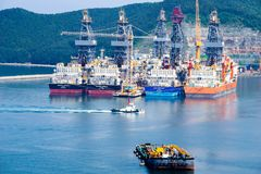 拖轮风帆通行证driil在大宇造船和船舶工程学DSME在Okpo市,韩国海湾运送  库存照片