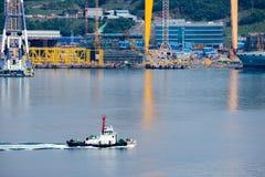 拖轮风帆通行证driil在大宇造船和船舶工程学DSME在Okpo市,韩国海湾运送  库存图片