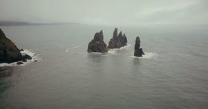 拖钓的鸟瞰图在冰岛在水中用脚尖踢山 在峭壁附近的直升机飞行在海在有雾的天 股票视频