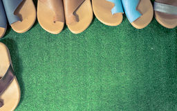 拖鞋舒适在人为草 免版税库存照片