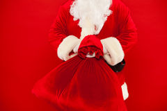 拖延红色大袋的圣诞老人手有很多礼物 免版税库存图片