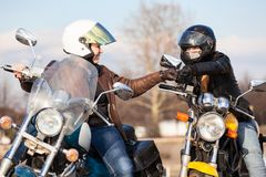 招呼两个妇女的骑自行车的人与拳头吹,通常摩托车骑士姿态  图库摄影