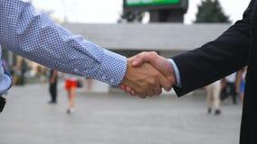 招呼两个的商人在城市环境里 室外企业的信号交换 震动男性武装外面 免版税库存图片