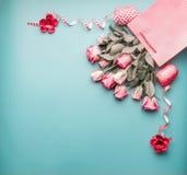 招呼在购物袋的桃红色苍白玫瑰束与在土耳其玉色背景的丝带,顶视图 免版税库存图片