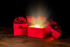 招呼有弓和奇迹光的被打开的箱子在木backgro 库存图片