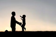 招呼爸爸剪影的愉快的幼儿赛跑 免版税库存照片