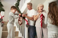 招呼的祖父母穿睡衣的激动的孙运行在拿着长袜的台阶下在圣诞节早晨 库存图片