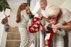 招呼的祖父母穿睡衣的激动的孙运行在拿着长袜的台阶下在圣诞节早晨 图库摄影