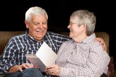 招呼看板卡的夫妇愉快的前辈 库存图片