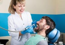 招待会是在医生审查在蛀牙的口腔的女性牙医 龋保护 医生投入 免版税库存图片