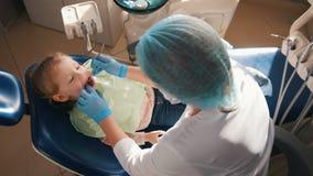 招待会的女孩牙医的, stomatologist审查儿童` s牙,逗人喜爱和淘气女孩微笑 影视素材